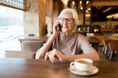 Positieve hogere ondernemer die telefonisch spreken stock afbeelding