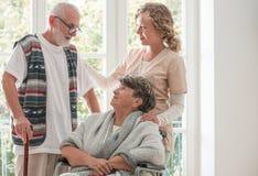 Positieve hogere vrouw op rolstoel met gevende verpleegster en bejaarde vriend met wandelstok stock afbeeldingen