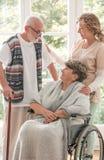 Positieve hogere vrouw op rolstoel met gevende verpleegster en bejaarde vriend met wandelstok stock foto's