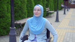 Positieve jonge gehandicapte vrouw in rolstoel het Moslimhijab openlucht glimlachen stock videobeelden
