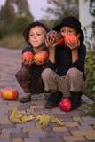Positieve jonge geitjes die met Halloween-pompoenen zitten Royalty-vrije Stock Foto