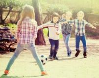 Positieve jonge geitjes die straatvoetbal in openlucht spelen Stock Fotografie
