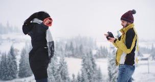 Positieve jonge mens en dame in verbazende mooie plaats op de bovenkant van sneeuwgebied, mooi sneeuwbos als achtergrond stock videobeelden