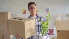 Positieve jonge sian mens met een bloem en een doos in zijn handbewegingen aan een nieuwe flat stock videobeelden