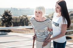 Positieve jonge vrijwilliger die het bejaarde helpen stock foto