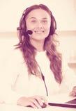 Positieve jonge vrouw die hands-free reeks gebruiken op kantoor Stock Afbeelding