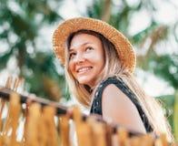 Positieve jonge vrouw het glimlachen zitting in hangmat op tropisch Palm Beach royalty-vrije stock fotografie