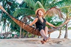 Positieve jonge vrouw in strohoed die in hangmat op het tropische strand slingeren royalty-vrije stock fotografie