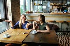 Positieve jonge vrouwen die bij koffie met koppen van koffie en het glimlachen zitten Stock Foto
