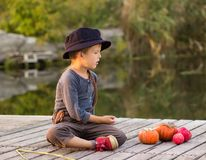 Positieve jongenszitting met Halloween-pompoenen Royalty-vrije Stock Afbeelding