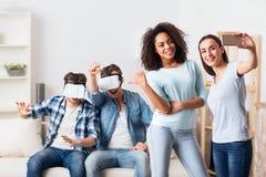 Positieve kerels die virtueel werkelijkheidsapparaat met behulp van Royalty-vrije Stock Afbeeldingen