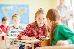 Positieve klasgenoten die bij les spreken royalty-vrije stock afbeelding