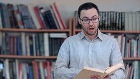 Positieve leraar of privé-leraar die Ta spreken een camera, die een boek in zijn handen houden stock footage