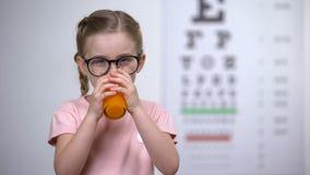 Positieve meisje het drinken wortel smoothie, gezonde voeding, oogvitaminen stock footage