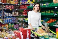 Positieve meisjesklant die smakelijke snoepjes in supermarkt zoeken Stock Fotografie