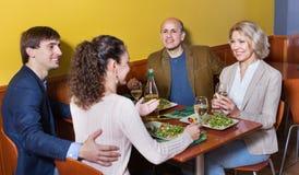 Positieve middenstandmensen die van voedsel en wijn genieten Royalty-vrije Stock Foto's