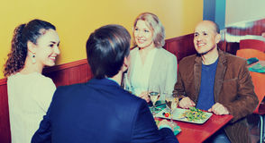 Positieve middenstandmensen die van voedsel en wijn genieten Stock Foto's