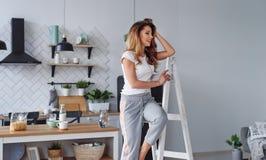 Positieve mooie jonge vrouw op een witte houten trapladder op de achtergrond van een modieuze moderne keuken royalty-vrije stock foto