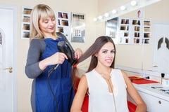 Positieve mooie vrouw in een herenkapper die haar haar krijgen dat op een vage achtergrond wordt geverft Hairstylingsconcept royalty-vrije stock foto's