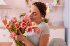Positieve opgetogen jonge vrouw die bloemen bekijken stock fotografie