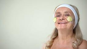 Positieve oude dame die het masker van het komkommergezicht, optimistische houding toepassen tegenover leeftijd royalty-vrije stock afbeeldingen