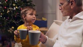 Positieve oude mens en zijn kleinzoon het drinken thee met koekjes stock videobeelden