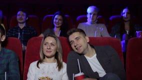 Positieve paar het drinken kola en het eten van popcorn in bioskoop stock footage