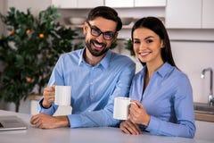 Positieve paar het drinken thee in de keuken stock afbeeldingen