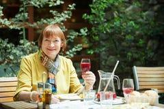 Positieve rijpe vrouw met glas wijn stock afbeelding