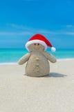 Positieve Sneeuwman in de hoed van Kerstmissanta claus bij oceaanstrand Stock Fotografie