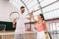 Positieve tennisspelers die hoogte vijf geven stock foto