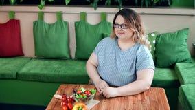 Positieve vette vrouw bij dieet het stellen met verse organische plantaardige saladezitting op lijst in koffie stock footage
