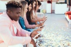 Positieve vrienden die in moderne mobiles typen royalty-vrije stock afbeeldingen