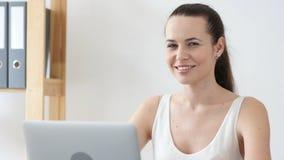 Positieve Vrouw die Camera op het Werk in Bureau bekijken royalty-vrije stock foto's