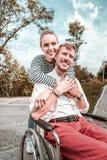 Positieve vrouw die haar steun tonen terwijl het koesteren van haar gehandicapte vriend royalty-vrije stock foto's