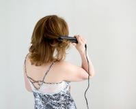 Positieve vrouw met het krullen van tang Royalty-vrije Stock Afbeelding