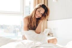 Positieve vrouw met hoofdkussenzitting in bed stock fotografie