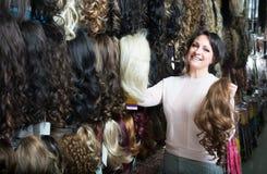 Positieve vrouwelijke klant die klem-in haaruitbreiding bij winkel selecteren royalty-vrije stock foto's