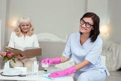 Positieve vrouwelijke verzorger die stof verwijderen stock foto