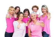Positieve vrouwen die en roze voor borstkanker stellen dragen Stock Fotografie