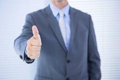 Positieve zakenman die met omhoog duim glimlachen Royalty-vrije Stock Foto's