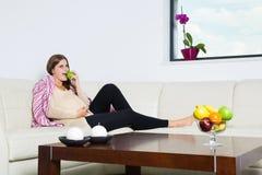 Positieve zwangere vrouw die groene appel eten Stock Foto