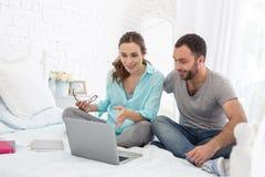 Positieve zwangere vrouw en man die lezing zien stock afbeeldingen