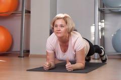 Position âgée moyenne concentrée de femme en position de planche photo stock