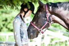 Position équestre de jeune dame près de son cheval de châtaigne images libres de droits