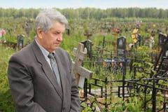 Position aînée triste sur le cimetière Photos libres de droits