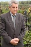Position aînée triste sur le cimetière et regard vers le bas Photos libres de droits