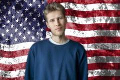 Position américaine belle d'étudiant universitaire sur le fond b de drapeau américain photos stock