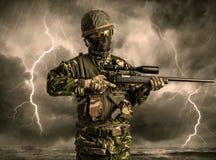 Position armée de soldat par temps obscur image stock