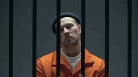 Position arrogante dangereuse de prisonnier derrière des barres et représentation des mains menottées banque de vidéos